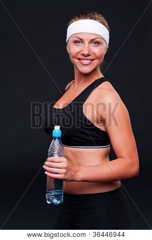 smiley fitness woman in black sportswear holding bottle of water over dark background