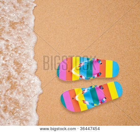 Colorful flipflop pair on sea beach