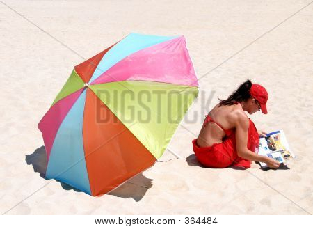 Young Woman In Red Bikini Sitting On Sandy Beach Reading Magazine