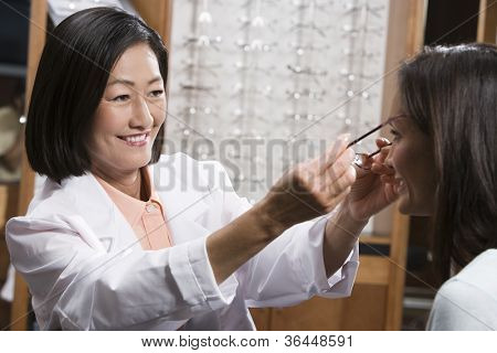 Happy female optometrist assisting patient