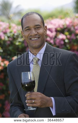 Happy middle aged businessman holding glass of wine