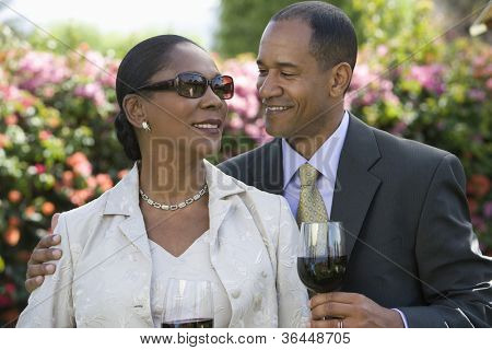 African American couple holding a wine glass while looking at each other