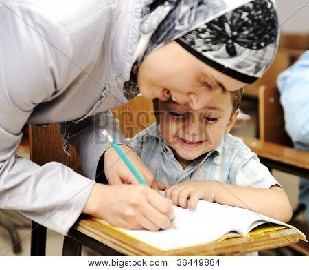 Muslim Arabic teacher working with little kid at school