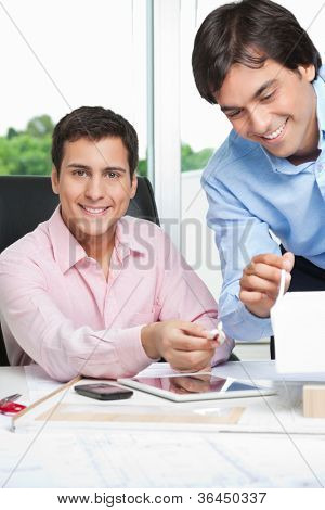 Portrait of happy young male architect at desk with colleague standing beside.