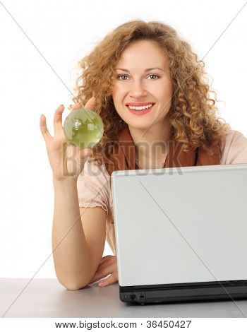 An attractive woman holding a glass globe and sitting on the desk with laptop, isolated on white background
