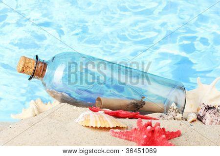 Botella de cristal con nota interior sobre arena, en el fondo del mar azul