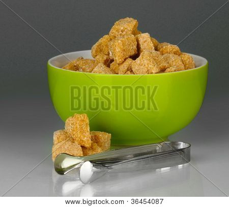 brown cane sugar cubes in bowl with sugar-tongs on grey background