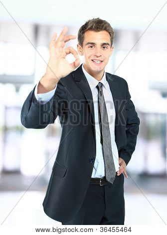 Portrait of smiling business man giving you OK sign in office