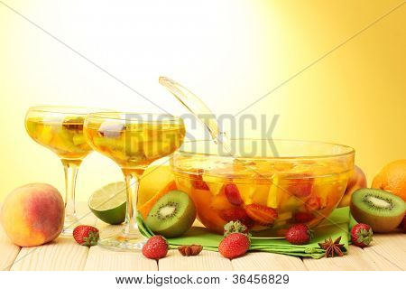 punch in bowl and glasses with fruits, on wooden table, on yellow background