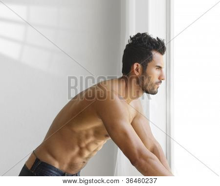 Portrait of a thoughtful handsome shirtless young man looking out of a window
