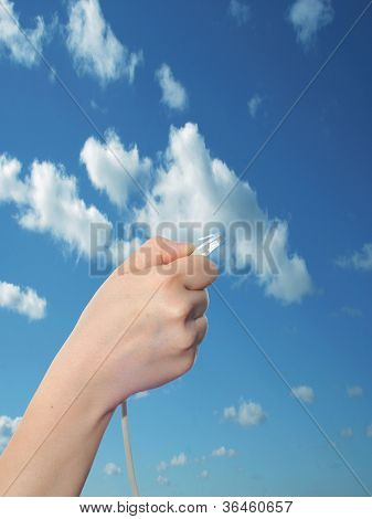 Concept or conceptual human or man hand holding a internet data cable in clouds over the blue sky, as a metaphor for plug,connection,technology,share,network,mobility,connectivity or communication