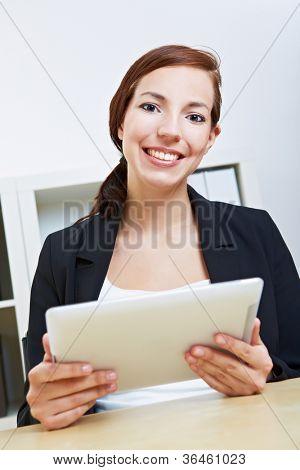Lächelnd geschäftsfrau mit ihrem Tablet-pc in einem Büro sitzen