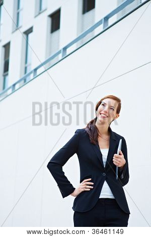 Happy business woman standing in front of a university