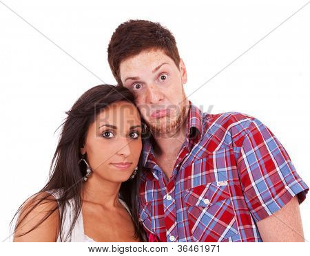 Image of beautiful fashion couple shot in studio - the boy has a goofy look on his face while she stays serious