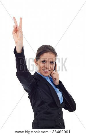 Portrait of young business woman smiling, showing victory sign and speaking at phone looking at the camera on white background