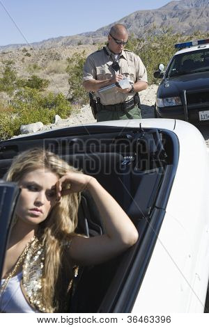 Portrait of an upset young woman with traffic cop writing ticket in the background