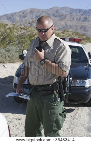 Traffic officer holding walkie-talkie
