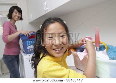 Portrait of a teenage girl helping her mother to wash clothes