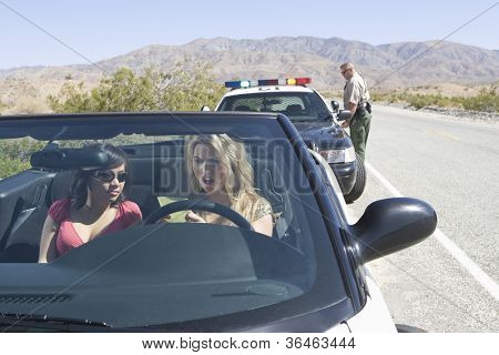 Young angry female friends reading ticket with traffic officer standing in the background
