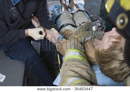 Firefighter and EMT doctor helping an injured patient in ambulance
