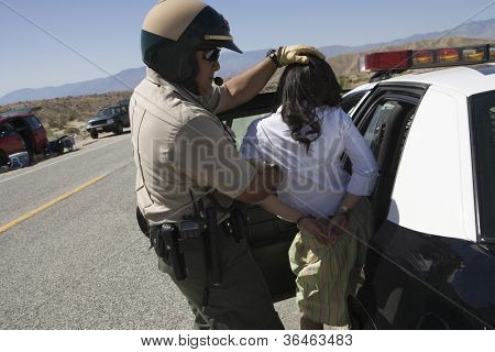 Traffic cop arresting young female drunken driver