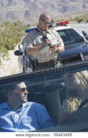 Couple in car looking at each other while traffic officer writing ticket in the background
