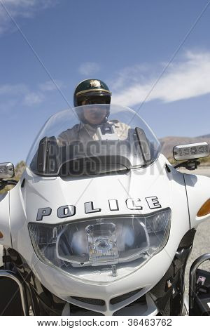Middle aged police officer riding motorbike