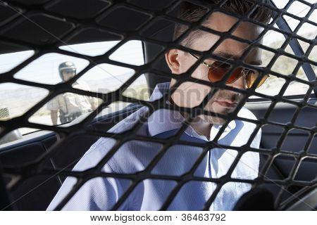 Criminal sitting in police car