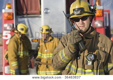 Portrait of a firefighter talking on radio with colleagues standing in the background