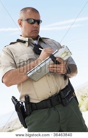 Middle aged traffic policeman writing on clipboard