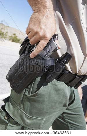Midsection of a policeman holding gun