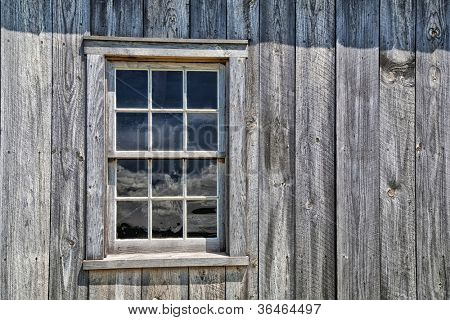 Window of an authentic wooden pioneer house. An example of an early pioneer homestead circa 1700 in rural Prince Edward Island, Canada.