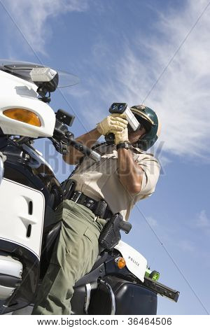 Middle aged traffic officer looking through radar gun from below