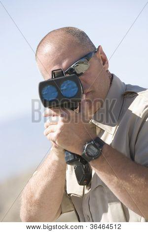 Portrait of a middle aged traffic officer looking through radar gun