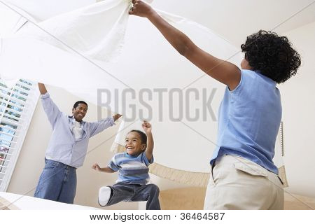 African American parents spreading bed sheet over son in bedroom