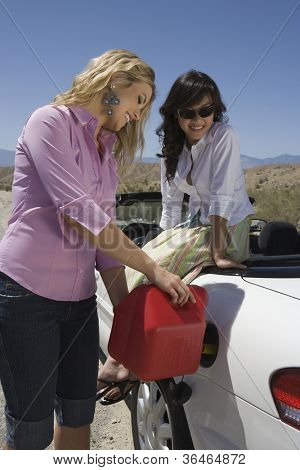 Happy young women refueling fuel in car