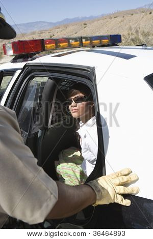 Arrested woman sitting in police car looking at traffic cop
