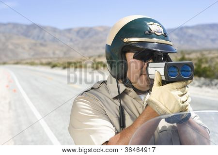Middle aged traffic officer looking through radar gun