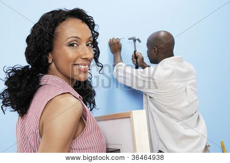 Portrait of happy African American woman holding picture frame with man hammering nails into wall