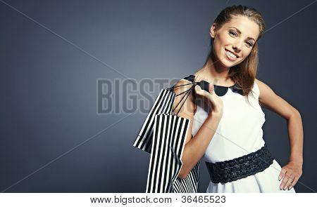 Mulher segurando sacolas contra um fundo cinza