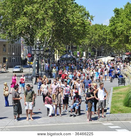BARCELONA, SPAIN - AUGUST 16: A crowd in La Rambla on August 16, 2012 in Barcelona, Spain. Thousands of people walk daily by this popular pedestrian mall 1.2 kilometer-long