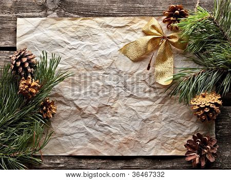 Crumpled paper sheet with gold bow, spruce twigs and pinecones on old wood. Sweet Xmas holiday background.