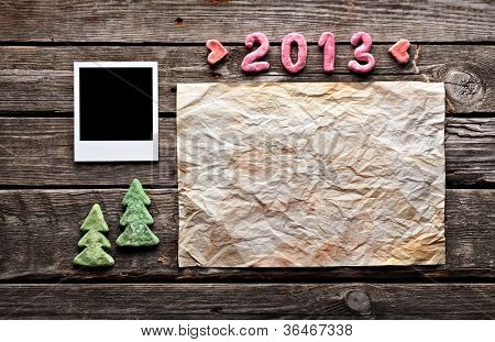 Sweet 2013 New Year holiday background. With blank instant photo frame, crumpled paper sheet, hearts and cute Christmas trees.
