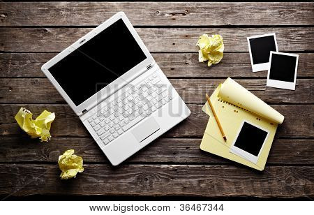 Laptop with blank instant photos and notepad with sheets of crumpled paper on old wooden table. Workplace writer.