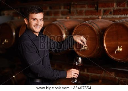 Sommelier pours wine from a barrel