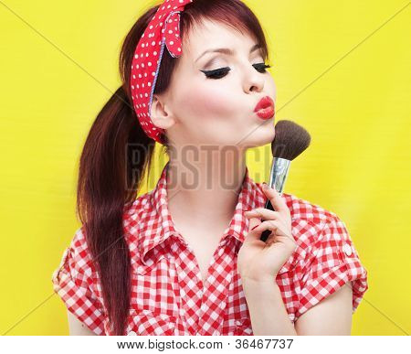 Cute pin up girl applying blusher