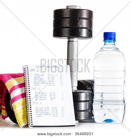 metal barbells with bottle of water, towel and week program
