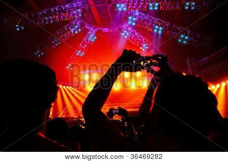 Rock concert, happy people silhouettes, raise up hands, disco party with large group of dancing man, bright colorful stage lights, active lifestyle, music entertainment, nightclub, night life concept