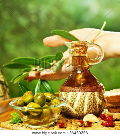 Homemade olive oil, woman's hand holding olive leaves branch, green fresh fruits in transparent glass bowls, healthy eating concept, food still life, organic nutrition, ripe vegetables, salad dressing