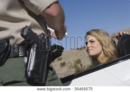 Young woman looking at traffic officer checking her license